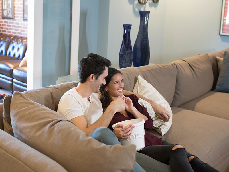 Couple watches movie on sofa with popcorn
