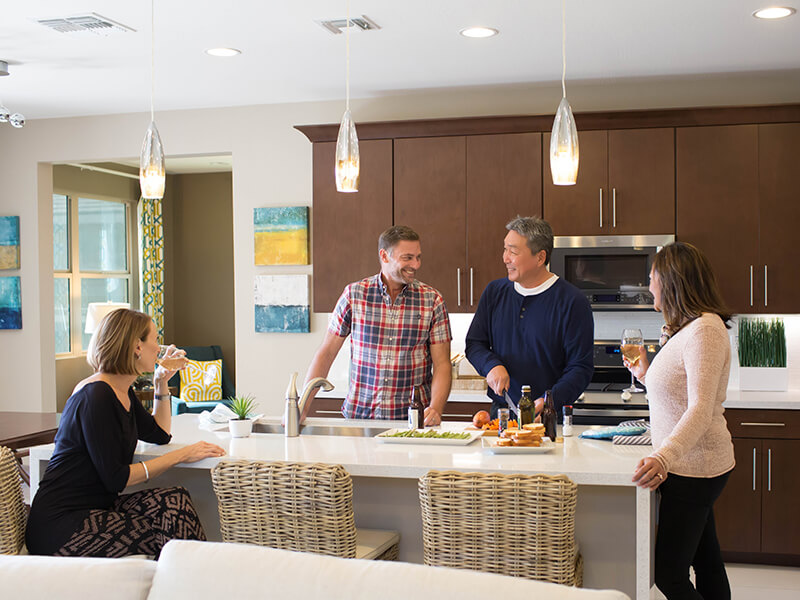 Two couples preparing dinner in the kitchen