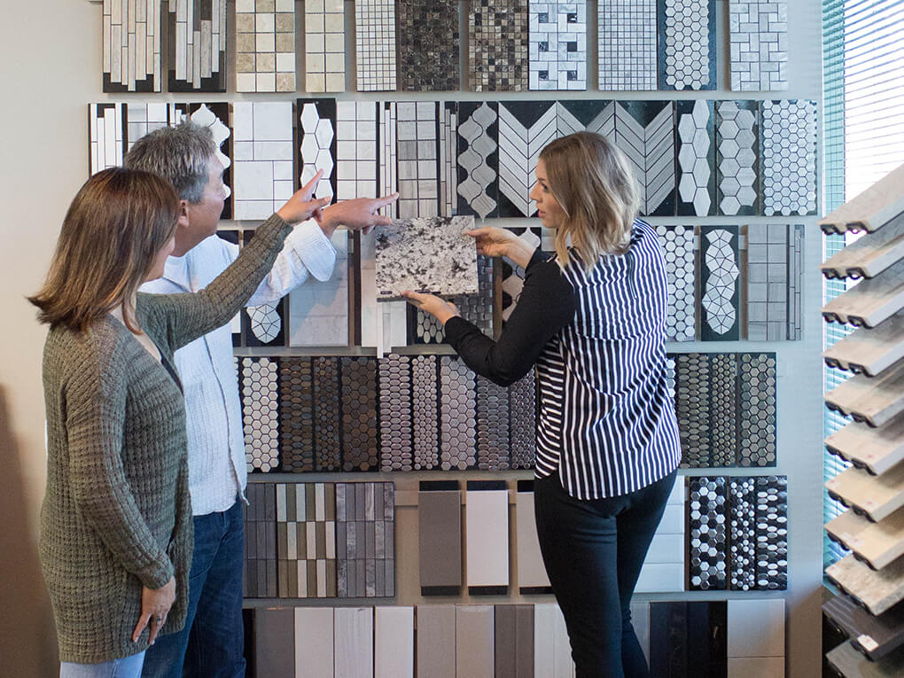 Couple looking at tile samples with a salesperson