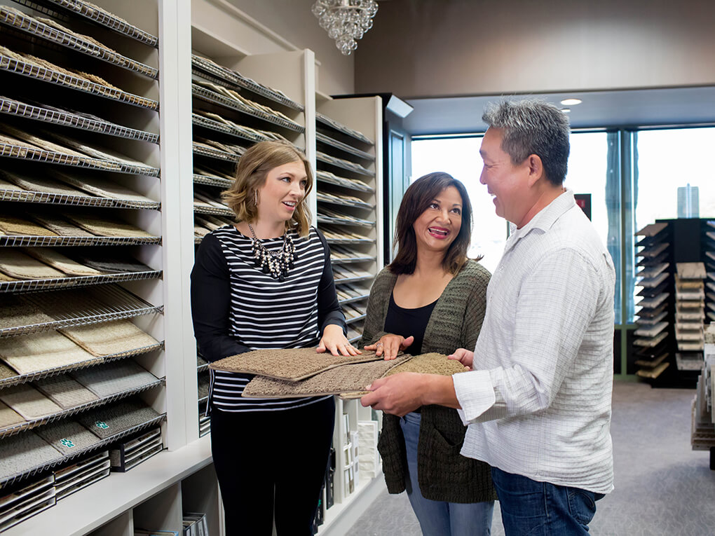 Couple and sales associate look at carpet samples