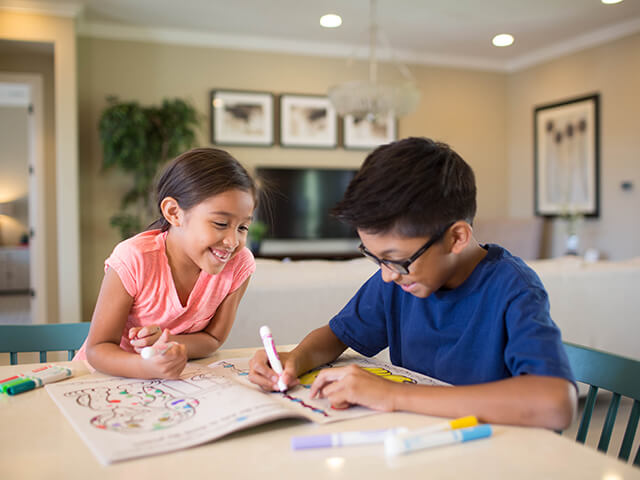 Children coloring at the kitchen table
