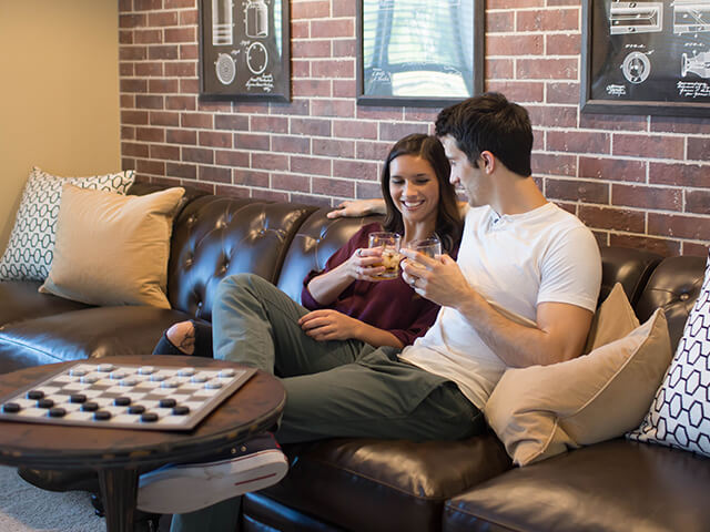Couple cheering each other on black leather sofa