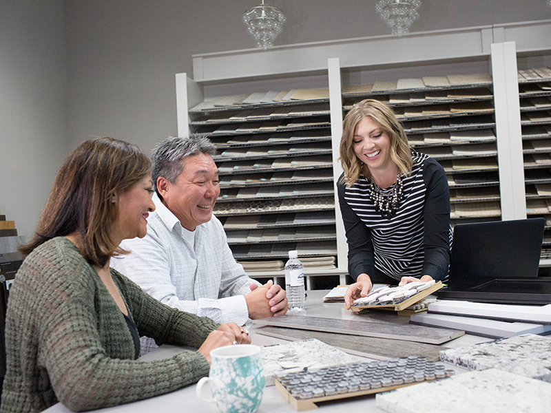 Couple looking at tile samples with salesperson