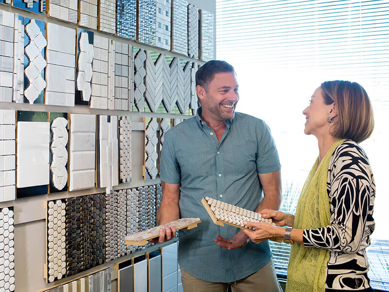 Woman looking at tile samples with salesperson