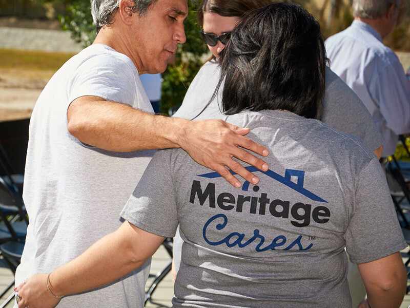 Woman wearing Meritage Cares t-shirt walking with a friend