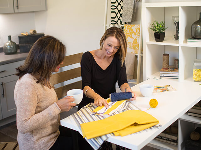 Customer and sales associate look at fabric samples