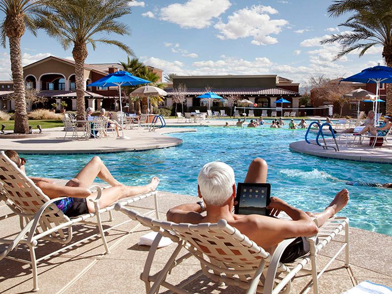 Man relaxing by pool with tablet