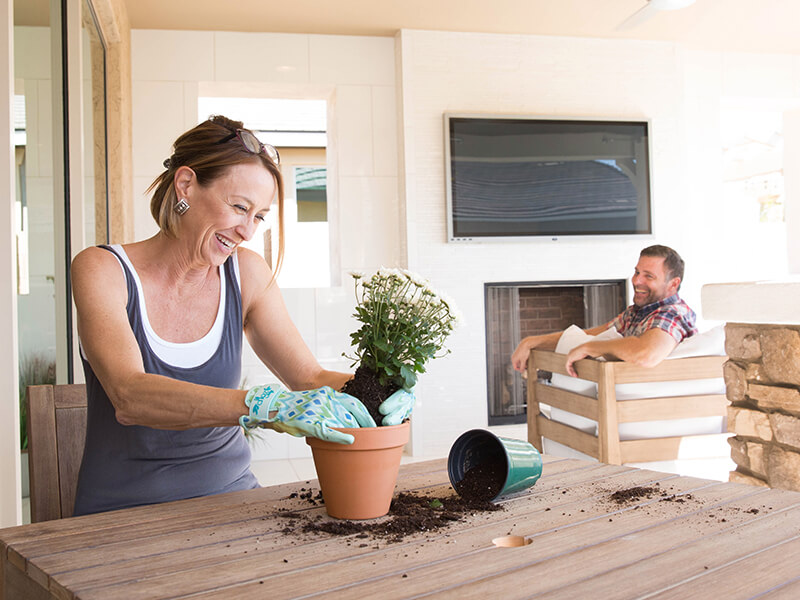Woman potting plants while husband sits on couch