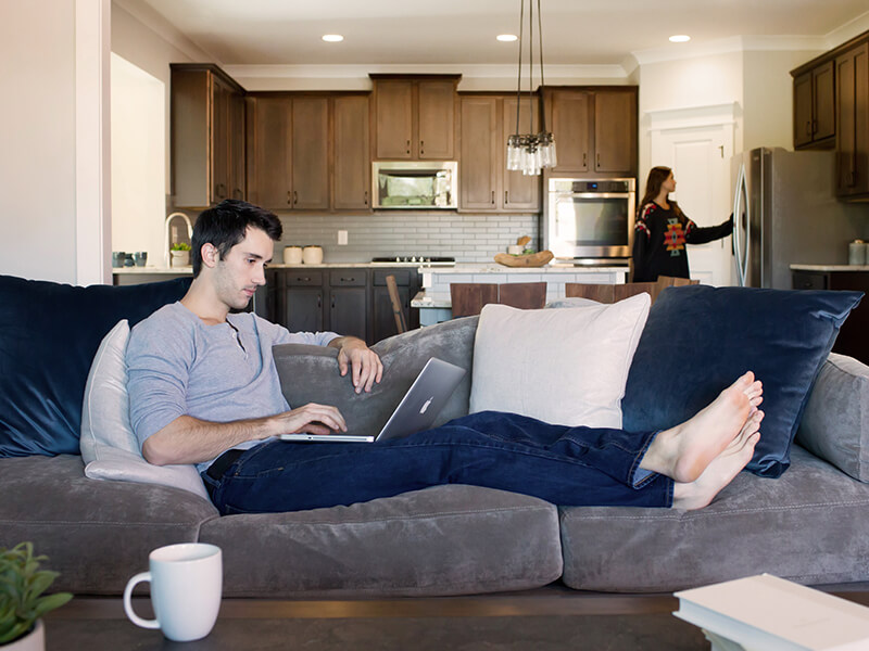 Man on couch submitting a claim on his computer