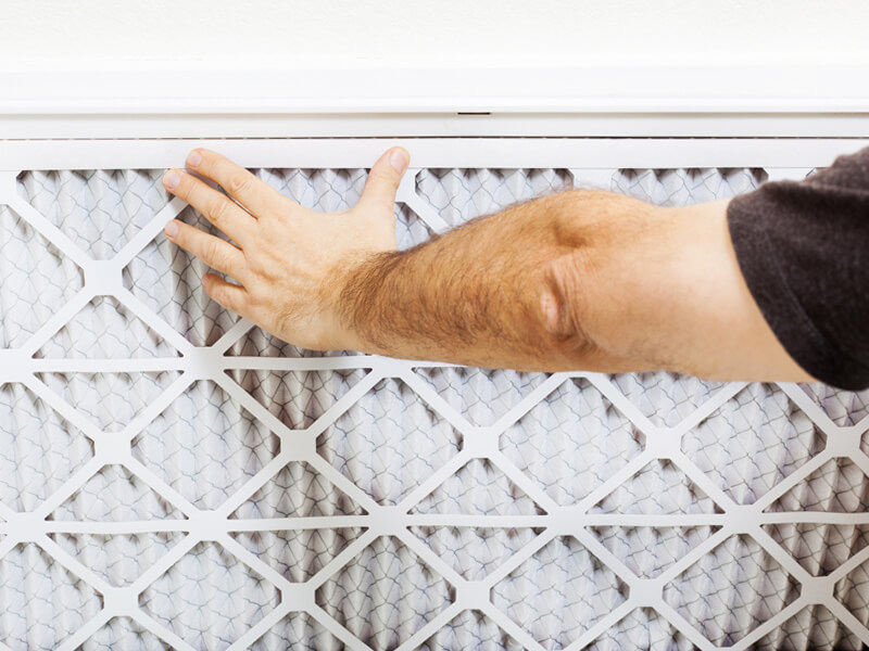 Person replacing air filters in a home
