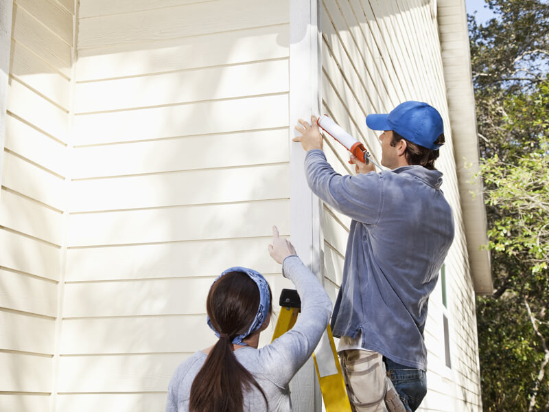 People inspecting exterior paint caulk