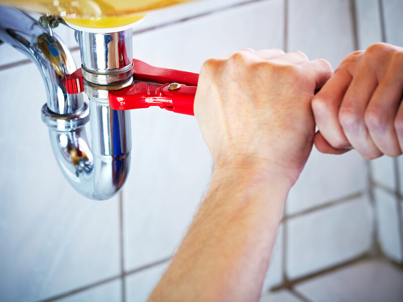 Person tightening a sink with a wrench