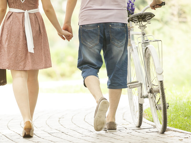 Couple walking with a white bicycle