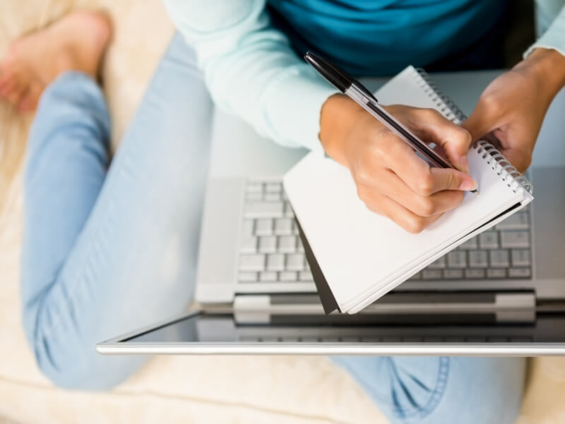 Woman taking notes from her laptop