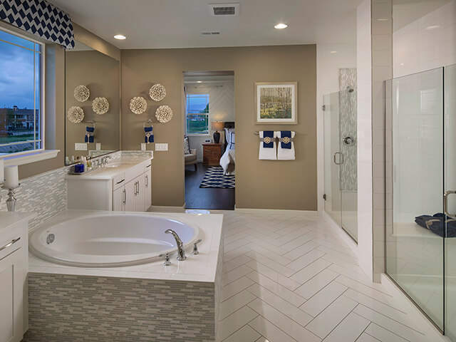 Bathroom with circular tub and beige wall