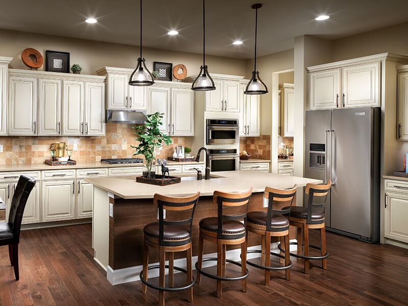 Kitchen with white cabinets hardwood floors and leather barstools