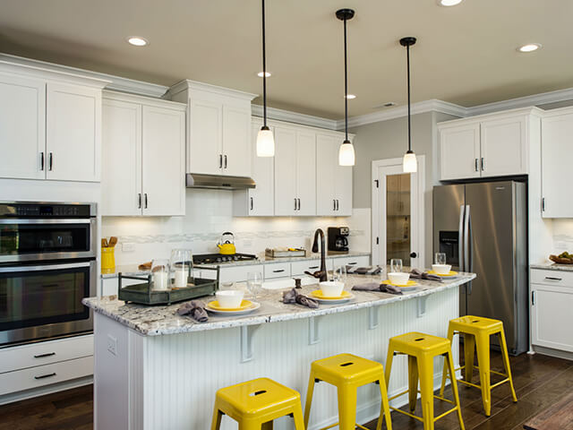 Kitchen with white cabinets, granite countertops and yellow bar stools