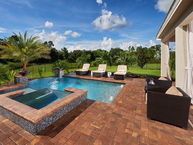 Brown stone pool area with jacuzzi